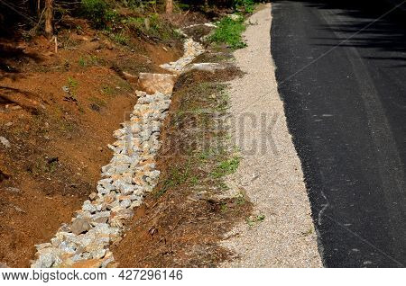 Renovation Of Asphalt Road In The Mountains. The Ditches Are Filled With Stones To Slow Down The Wat
