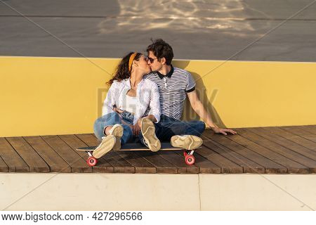 Trendy Young Couple Of Skateboarders Together Sit On Longboard Kissing. Romantic Date Of Millennial