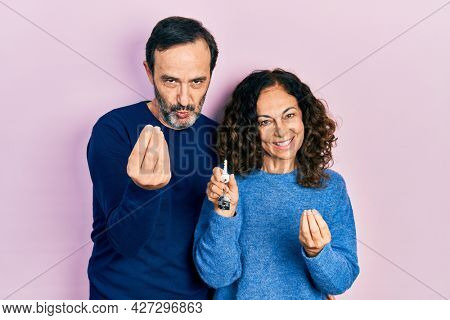 Middle age couple of hispanic woman and man holding keys of new home doing money gesture with hands, asking for salary payment, millionaire business