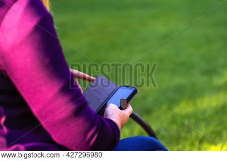 Defocus Close-up Female Hands Searching On The Phone Outside, Outdoor. Woman In Purple Blouse Using