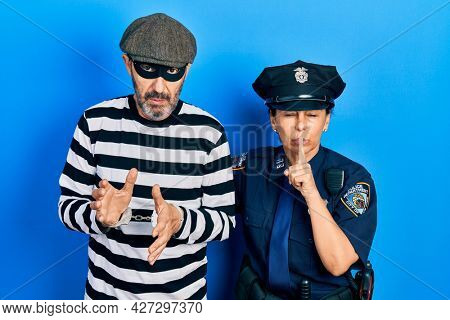 Middle age couple of hispanic woman and man wearing thief and police uniform asking to be quiet with finger on lips. silence and secret concept.