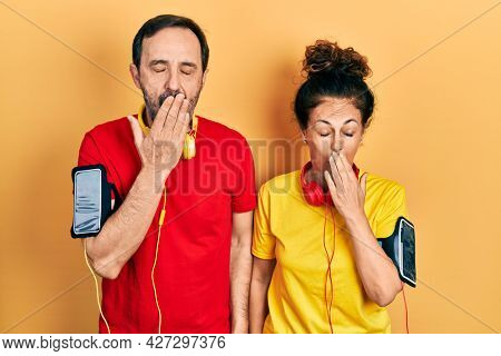 Middle age couple of hispanic woman and man wearing sportswear and arm band bored yawning tired covering mouth with hand. restless and sleepiness.