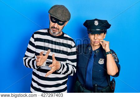 Middle age couple of hispanic woman and man wearing thief and police uniform mouth and lips shut as zip with fingers. secret and silent, taboo talking