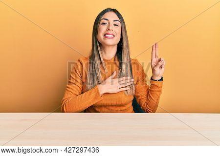 Young hispanic woman wearing casual clothes sitting on the table smiling swearing with hand on chest and fingers up, making a loyalty promise oath