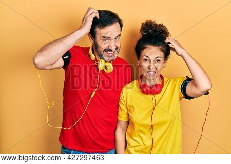 Middle age couple of hispanic woman and man wearing sportswear and arm band confuse and wonder about question. uncertain with doubt, thinking with hand on head. pensive concept.