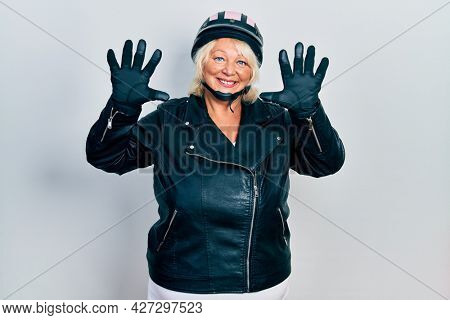 Middle age blonde woman holding motorcycle helmet showing and pointing up with fingers number ten while smiling confident and happy.