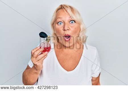 Middle age blonde woman holding perfume scared and amazed with open mouth for surprise, disbelief face