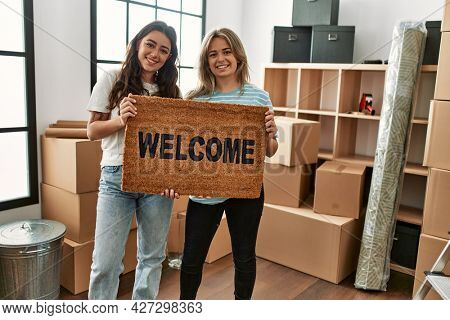 Young beautiful couple smiling happy holding welcome doormat at new home.