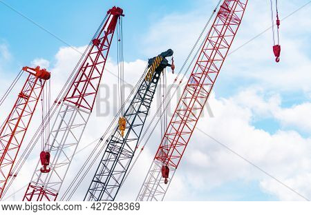 Crawler Crane Against Blue Sky And White Clouds. Real Estate Industry. Red Crawler Crane Use Reel Li
