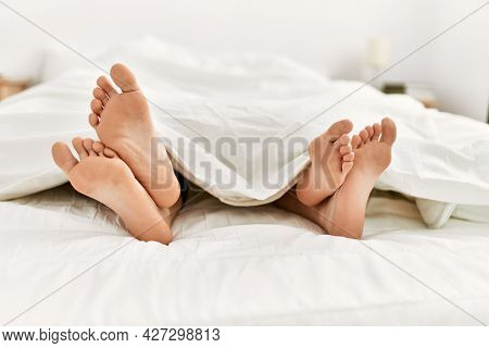 Couple feet under sheets on the bed at home.