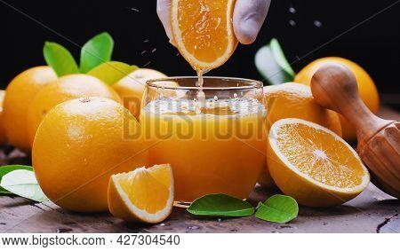 Yellow orange fruits and fresh orange juice. Squeezing out the fresh orange.