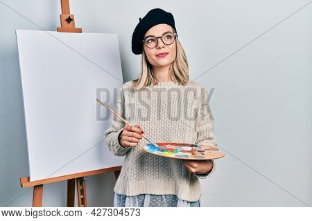 Beautiful caucasian woman drawing with palette on easel stand smiling looking to the side and staring away thinking.
