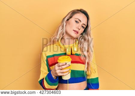 Beautiful young blonde woman drinking cup of coffee wearing headphones looking sleepy and tired, exhausted for fatigue and hangover, lazy eyes in the morning.