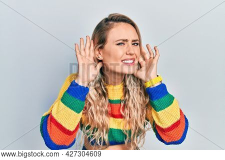 Beautiful young blonde woman wearing colored sweater trying to hear both hands on ear gesture, curious for gossip. hearing problem, deaf