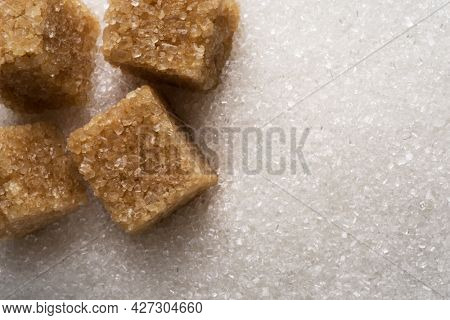White refined sugar granules and brown sugar cubes close-up. Food background.