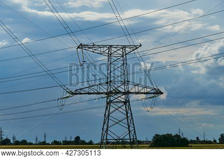 High-voltage electric lines, towers and industrial infrastructure against the blue sky