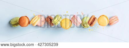 Vintage pastel colored French macaroons or macarons in motion falling on light blue background.Food banner Macaron Sweets