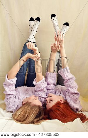 Two Young Girls Are Lying And Talking Down With Legs Up