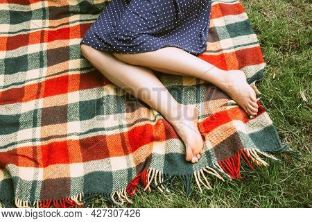 Beautiful Female Legs On A Bright Checkered Plaid. Summer In The Park. Front View