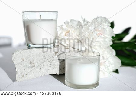 White Scented Soy Wax Candles On A Natural Stone And Peony Flowers. Floral Fragrance For Cozy Home.