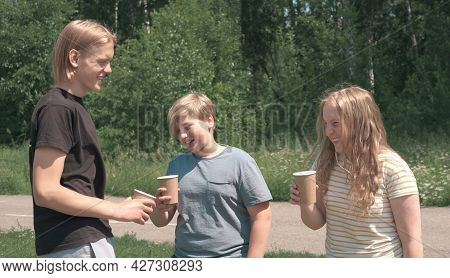 Caucasian Teenagers Having Fun Drinking Coffee To Go In A Park. Talking And Laughing Boys And Girl,