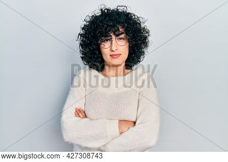 Young middle east woman with arms crossed gesture relaxed with serious expression on face. simple and natural looking at the camera.