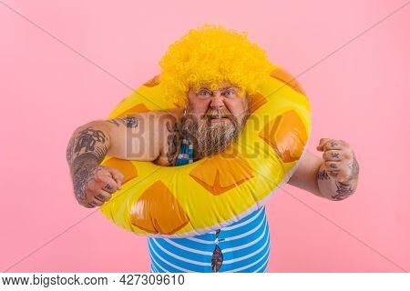 Fat Angry Man With Wig In Head Is Ready To Swim With A Donut Lifesaver