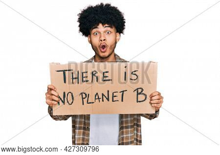 Young african american man with afro hair holding there is no planet b banner scared and amazed with open mouth for surprise, disbelief face