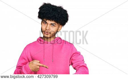 Young african american man with afro hair wearing casual pink sweatshirt in hurry pointing to watch time, impatience, upset and angry for deadline delay