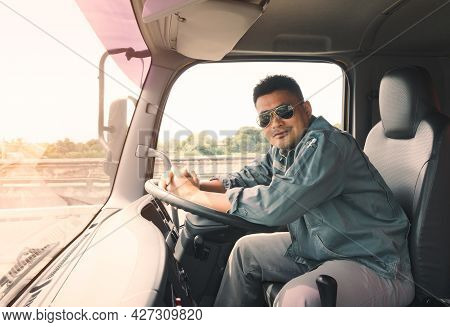 Semi-truck Driver Wearing Sunglasses Happy Smiling In Cockpit.   Mature Young Man Asian Transport Bu