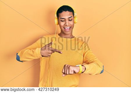 Young african american guy listening to music using headphones in hurry pointing to watch time, impatience, upset and angry for deadline delay