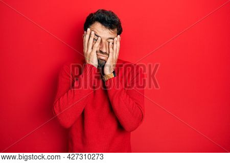 Handsome man with beard wearing casual red sweater tired hands covering face, depression and sadness, upset and irritated for problem
