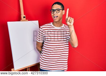 Young african american guy standing by painter easel stand smiling with an idea or question pointing finger up with happy face, number one