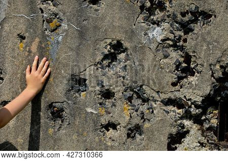 Shot Down Concrete Fortification With A Machine Gun. Bullet Holes Pointed By The Hand Of A Little Bo