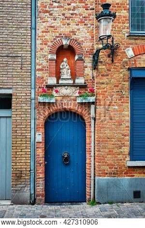 Door and window of an old house with Virgin Mary statue, Bruges (Brugge), Belgium