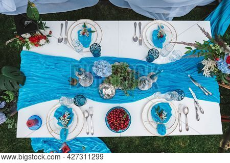 White Banquet Table Covered With Blue Cloth, Served With Plates, Cutlery, Glasses, Candles And Flowe