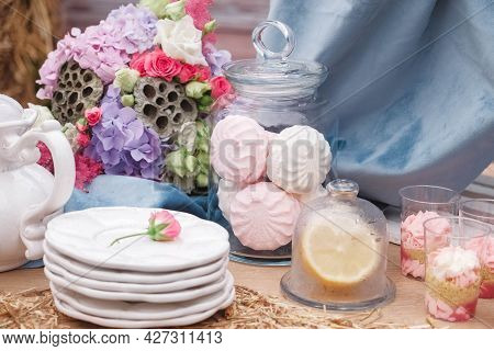 Wedding Candy Bar In Rustic Style Decorated With Plates, Cutlery, Glasses, Candles And Flower Arrang