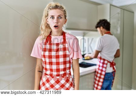 Young caucasian woman wearing apron and husband doing housework washing dishes scared and amazed with open mouth for surprise, disbelief face