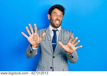 Handsome man with beard wearing business suit and tie afraid and terrified with fear expression stop gesture with hands, shouting in shock. panic concept.