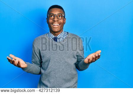 Young african american man wearing business style and glasses celebrating mad and crazy for success with arms raised and closed eyes screaming excited. winner concept