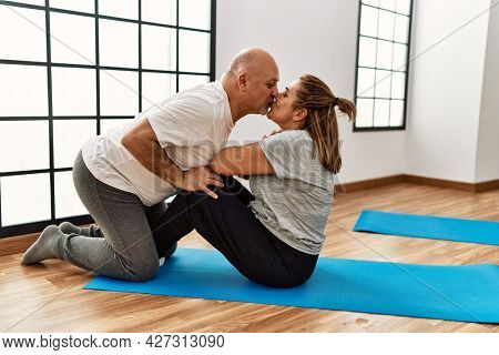 Middle age hispanic couple training abs exercise and kissing at sport center.