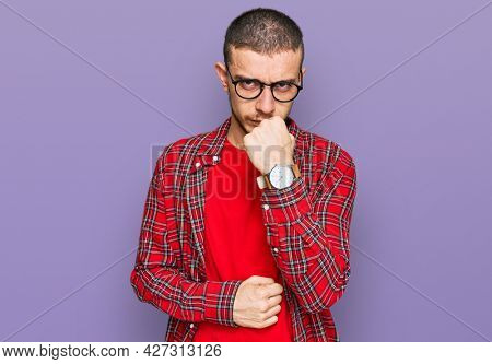 Hispanic young man wearing casual clothes ready to fight with fist defense gesture, angry and upset face, afraid of problem