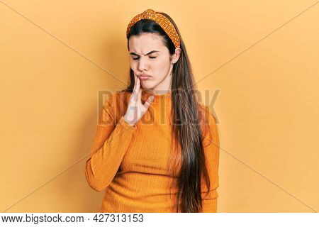 Young brunette teenager wearing casual yellow sweater touching mouth with hand with painful expression because of toothache or dental illness on teeth. dentist