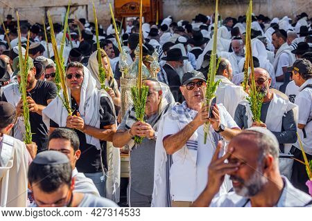 JERUSALEM, ISRAEL - SEPTEMBER 26, 2018: The Jews of ritual clothes - tallit hold four ritual plants. The area in front of Western Wall of Temple filled with people. Blessing of the Kohanim,