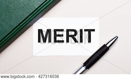 On A Light Gray Background Lies A Pen, A Green Notebook And A White Card With The Text Merit. Busine
