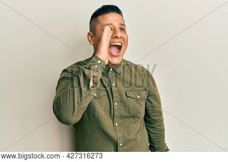 Young latin man wearing casual clothes shouting and screaming loud to side with hand on mouth. communication concept.