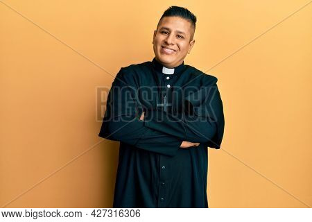Young latin priest man standing over yellow background happy face smiling with crossed arms looking at the camera. positive person.