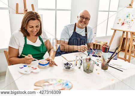 Middle age hispanic painter couple smiling happy painting at art studio.