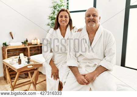 Middle age hispanic couple wearing bathrobe at wellness spa with a happy and cool smile on face. lucky person.