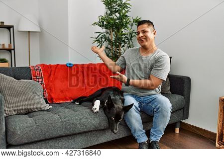 Young latin man and dog sitting on the sofa at home inviting to enter smiling natural with open hand